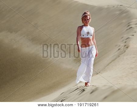young happy woman walking on sand dunes in summer