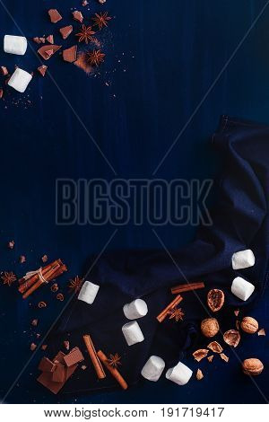 Dark copy space frame with sweets: cocoa powder, marshmallows, walnuts, chocolate and cinnamon on a black background