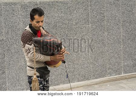 Tehran IRAN - May 2 2017 a street musician entertain people in front of metro station by decorated bagpipe instrument.