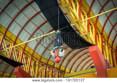 Labuan,Malaysia-May 21,2017:Adventurer climber with climbing equipment on rope upside down an indoor rock climbing in Labuan,Malaysia.