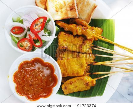 Pork satay Thai street food grilled pork served with peanut sauce or sweet and sour sauce on white plate.
