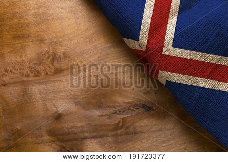 Flag Iceland on a wooden background of rough fabric.