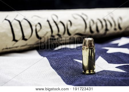 The United States Constitution rolled up next to a bullet rests on an American flag and symbolizes the right to bear arms.