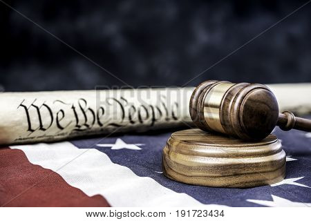 The United States Constitution rolled up on an American flag with a gavel in the foreground. Room for copy along the top half of the image.