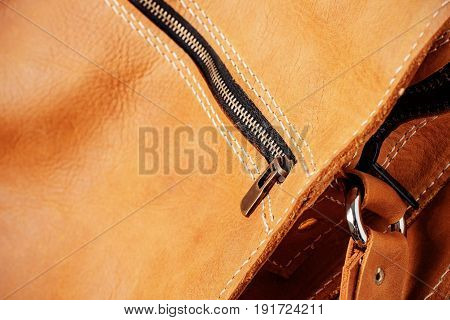 Zipper on a brown leather bag with texture of details.