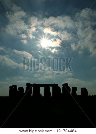 Historic Stonehenge in Silhouette against the Sun on a Partly Cloudy Day