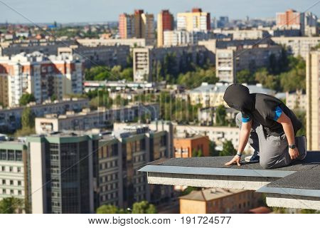 Roofer on the edge of the roof. A man looks down from a high-rise building. Courage and adrenaline. Roofing. Man is unrecognizable.