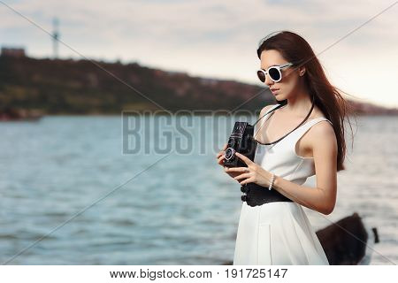 Retro Woman with Vintage Photo Camera on a Beach