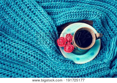 Turquoise knitted woolen scarf a cup of coffee on saucer three pink roses vintage style