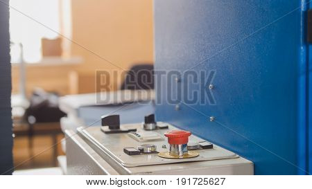 Red button on folding machine - printing polygraph industry, close up - telephoto