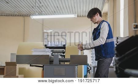 Worker and printing machine, polygraph industry - close up, telephoto