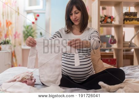 Pregnant woman with big belly at home.