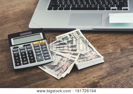 Money Japanese yen banknotes with calculator and notebook computer on wood table