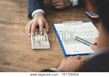 Businessman giving money Japanese yen banknotes while making contract - loan bribery and corruption concepts