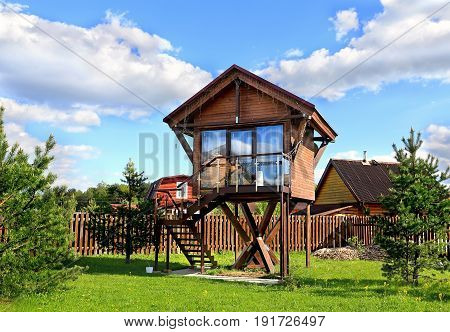 Wooden cottage of the brown color raised above the ground on metal piles