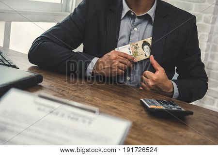 Businessman putting money South Korean won banknotes into his suit pocket - bribery and corruption concept