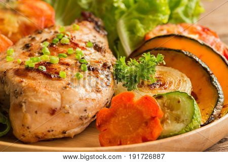 Homemade chicken breast barbecue on wood plate served with grilled vegetables. Delicious chicken barbecue and grilled vegetables for lunch or dinner. Roast chicken breast in close up concept. Chicken breast steak or pork steak.