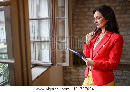 Female employee standing alone near open window and working
