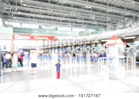 Blurred image of passengers wait in a queue for check-in in an airport.
