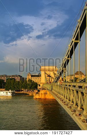 BUDAPEST. HUNGARY - JULY 26 2016: A golden hour of the evening at Budapest after rain a view to Chain Bridge and a rainbow between the clouds at the background Hungary.
