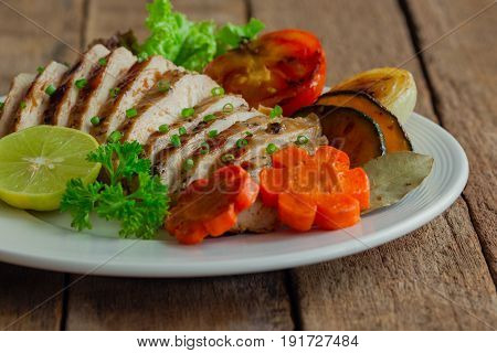 Sliced chicken breast barbecue on white plate served with grilled vegetable. Delicious chicken breast steak and salad for dinner. Homemade chicken breast barbecue on wood table for background. Chicken breast steak or pork steak.
