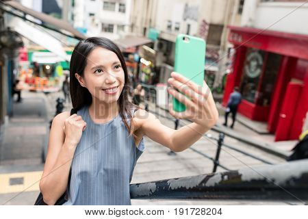 Woman taking photo with cellphone in Pottinger Street