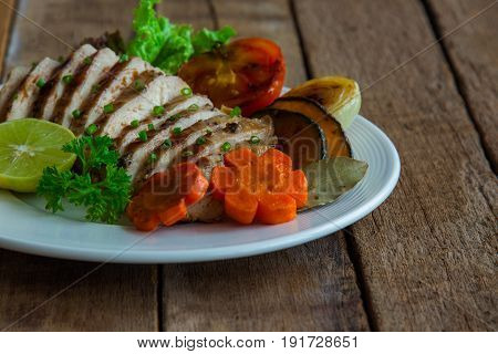 Sliced chicken breast barbecue on white plate served with grilled vegetable. Delicious chicken breast steak and salad for dinner. Chicken breast barbecue or chicken steak on wood table for background in extremely underexposed concept.