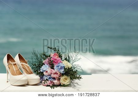 Shoes And Bouquet Stand On The White Balcony In The Front Of Great Landscape