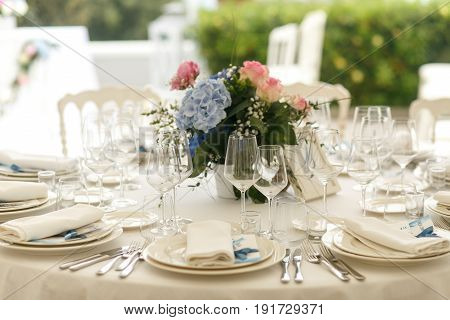 Elegant Glassware Stands On The Table Beautified With Blue Bouquet