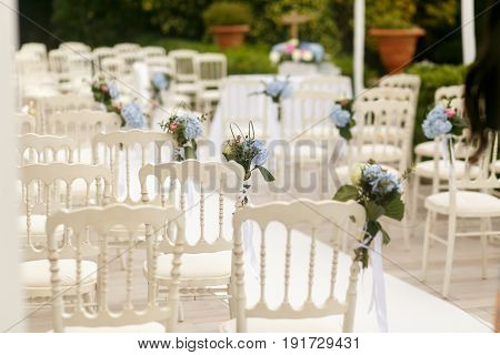 Delciat Bouquets Of White Hydrangeas Pinned To The Chairs
