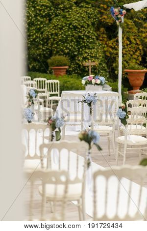 Look From Behind The White Pillar On The Chairs With Flowers Waiting For An Engagement Ceremony