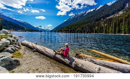 Senior woman sitting on a log enjoying the view of the snow capped peaks around Duffey Lake with Mount Rohr at the south end of the lake. Duffey Lake is along Highway 99 between Pemberton and Lillooet
