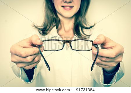 Female oculist doctor giving glasses to patient - eye care concept - retro style