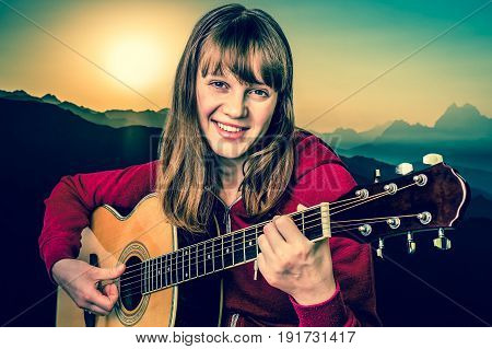 Young girl playing acoustic guitar in mountains at the sunset - retro style