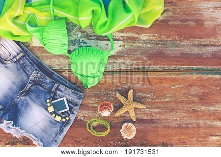 Summer women's clothing and accessories: denim shorts, bathing suit, pareo, shells, mobile phone. Top view. Toned image.