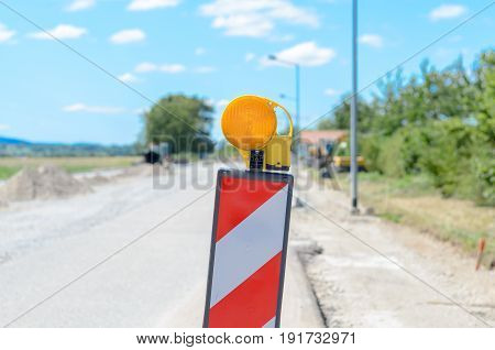 Chevron and warning light at the side of a road warning of roadworks ahead in a close up view on a rural route