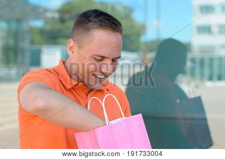 Happy Young Man Delving In A Shopping Bag