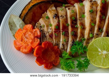 Sliced chicken breast barbecue on white plate served with grilled vegetable. Delicious chicken breast steak and salad for dinner. Homemade chicken breast barbecue on granite table background. Chicken barbecue of pork steak in close up view.