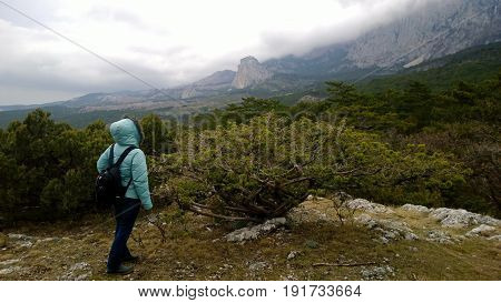 A woman with a backpack stands on a picturesque hilltop and looks into the distance at the mountains. Cloudy foggy weather. Side view