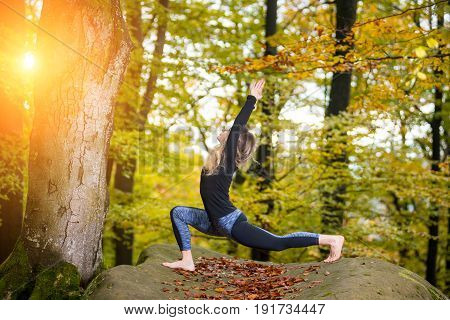 Beautiful Young Woman Is Practicing Yoga And Doing Asana Virabhadrasana 1 - Beautiful Young Woman Is