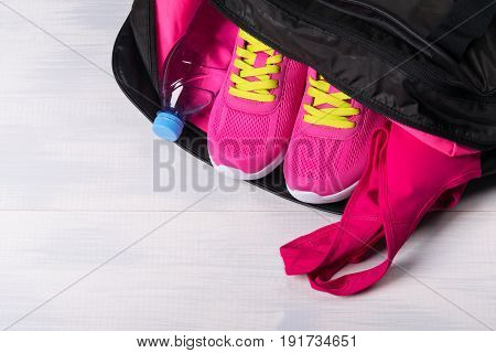 Sports things pink color for sports in a bag on a light background