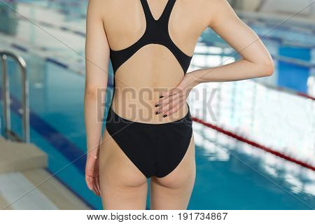 Close Up Of Swimmer Girl With Pain In The Small Of The Back. Young Sportsman Woman With Back Pain