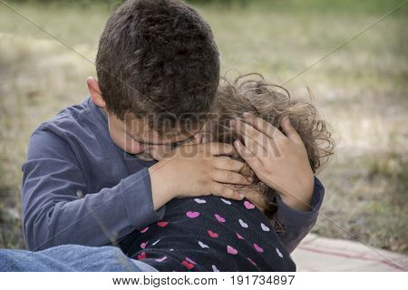 In the summer the elder brother comforts the little sister and embraces her.