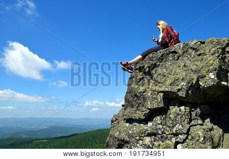 Girl sitting on rock. Relaxation at the top of Grosser Arber mountain in National park Bayerische Wald, Germany.