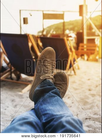 Men legs in sneakers close up on a background of deckchairs on the beach. Holiday background