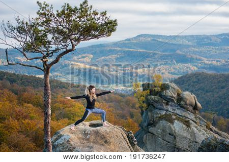 Sporty Attractive Female Is Practicing Yoga And Doing Asana Virabhadrasana 2 On The Top Of The Mount