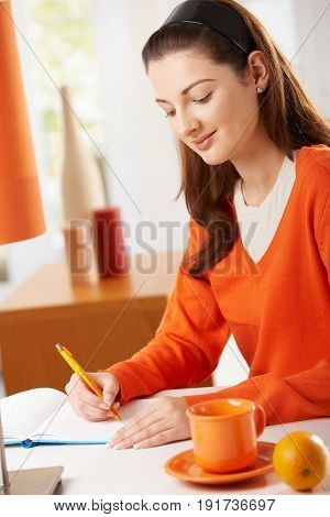 Young woman sitting at desk at home, writing notes to diary, looking down, smiling.