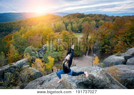 Attractive Young Woman Is Practicing Yoga And Doing Asana Virabhadrasana 1 On The Top Of The High Ro