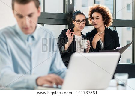 Two young women laughing while talking in the office behind their male colleague