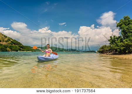 Happy young woman paddling a canoe on shallow water during vacation in an idyllic travel destination from Indonesia